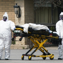 Workers wearing protective gear remove bodies of people who have died from COVID-19 from a New Jersey nursing home morgue
